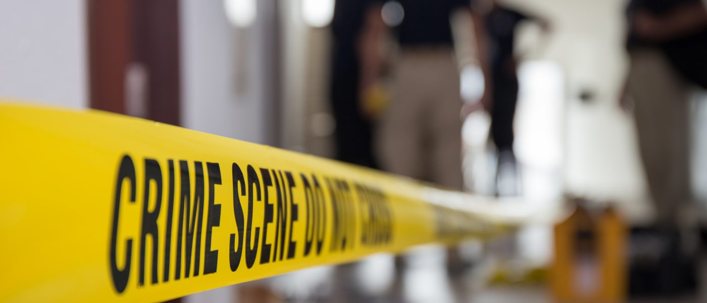 crime scene tape in building with blurred forensic team